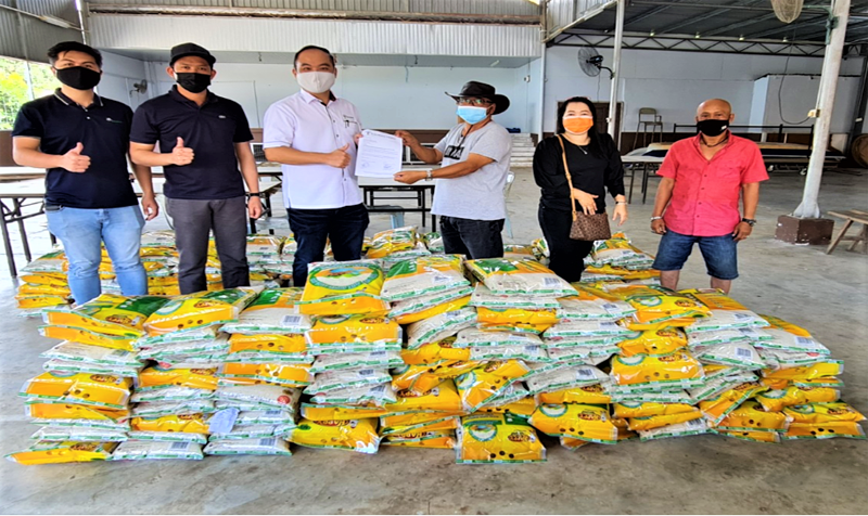 Kaliman Timber Corporation Sdn Bhd director Toh Kok Kwang (third left) hands over food assistance to Kampung Blimbin Krokong's community leader as others look on.